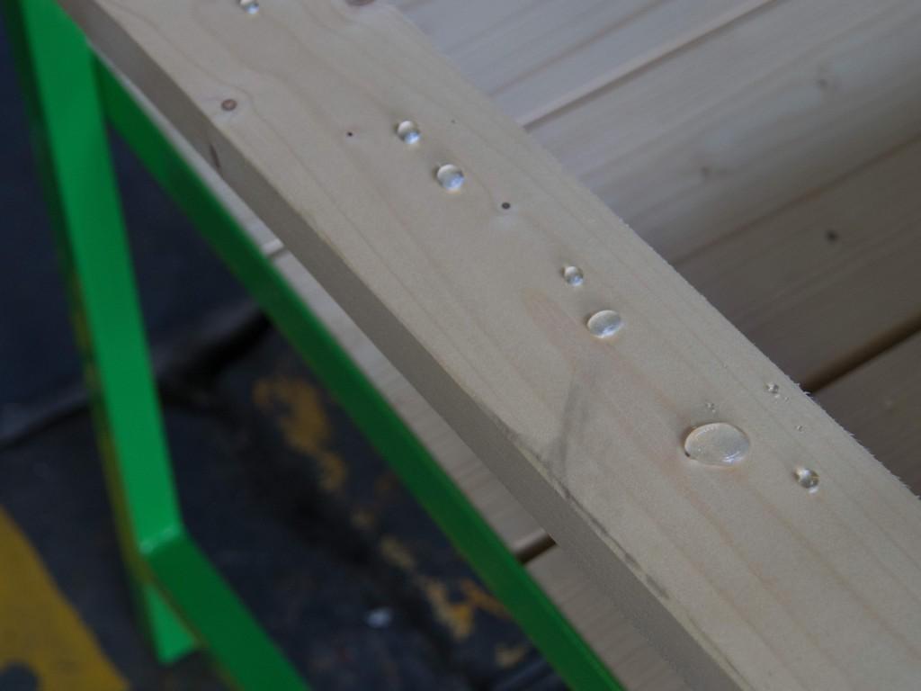 Bunt lackiertes Metall und wasserabweisendes Massivholz - Detailaufnahme