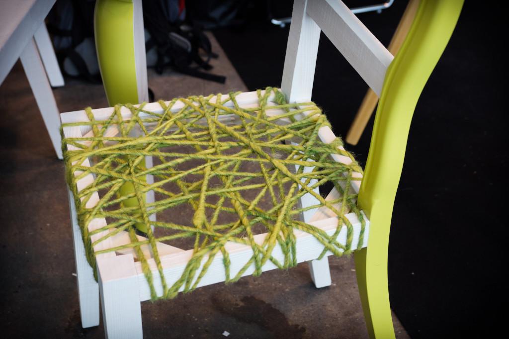 Die Sitzfläche des traditionell getischlerten Design-Stuhls aus weißem Holz ist unregelmäßig mit dicker, hellgrüner Wolle bespannt